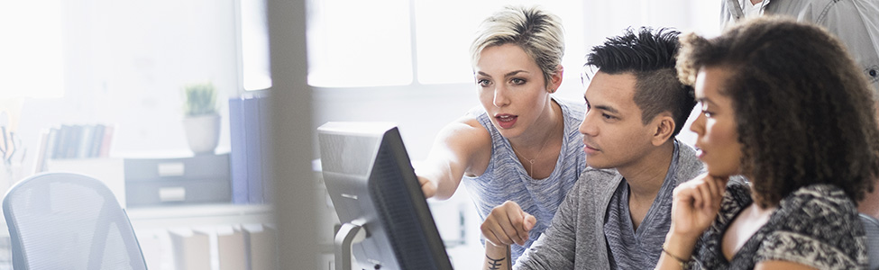 woman showing students something on computer